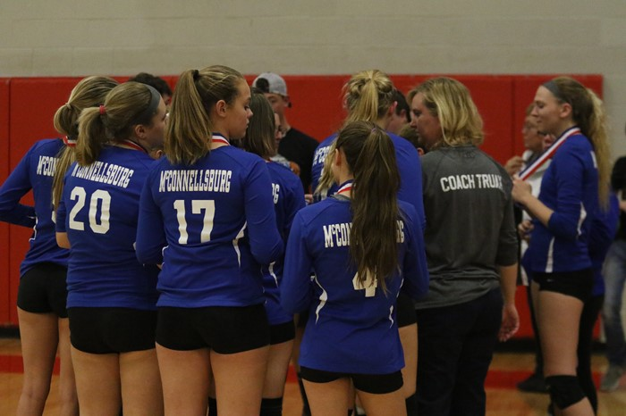 Volleyball team in huddle after receiving District Runner Up medals